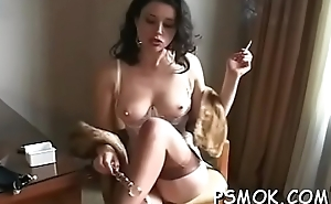 Busty lover playing upon her titties whilst smoking a cigarette